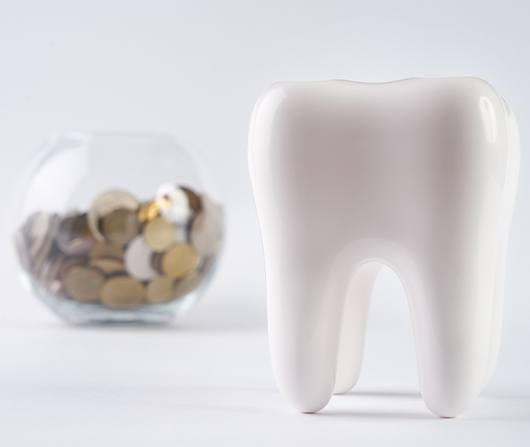giant plastic tooth with bowl of coins in back