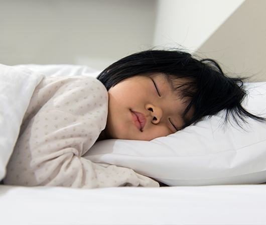 child fast asleep in bed