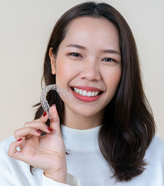 woman smiling bright holding invisalign tray
