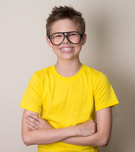 young boy in yellow shirt smiling big with braces