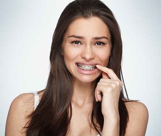 woman pointing to braces in pain