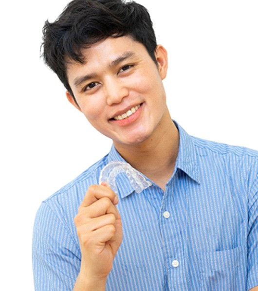A male teenager holding a clear aligner and smiling as he continues his treatment with Invisalign in Lakewood