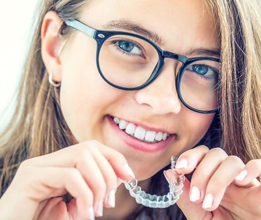 A young girl with glasses prepares to insert her Invisalign aligner into her mouth