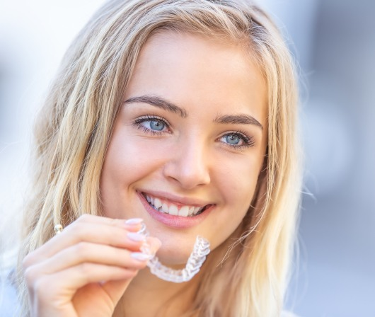 blonde woman holding invisalign