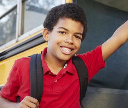 young boy leaning against school bus with braces