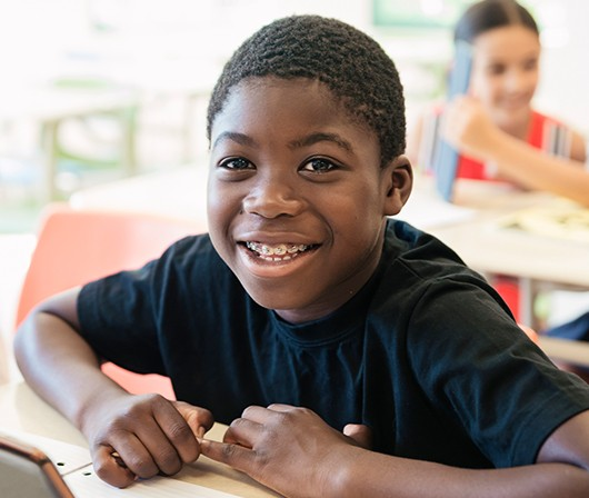 Young boy with braces in classroom at desk