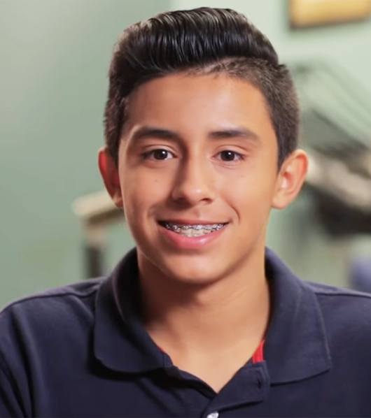 teen boy in polo shirt with braces smiling